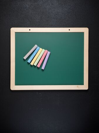 View of a group of chalks and a green blackboard.