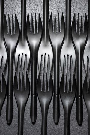 Disposable plastic cutlery on a black table.