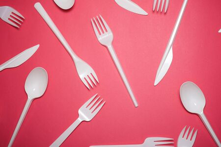 Disposable plastic cutlery on a pink table.