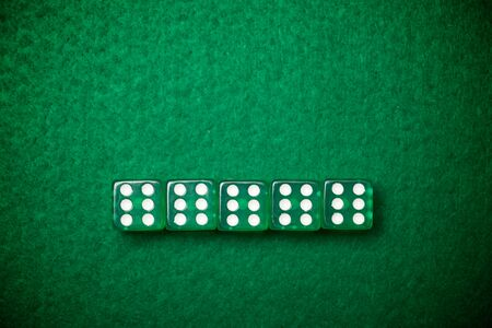 Casino dices on a green felt.