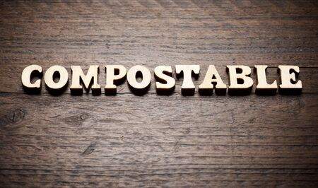 Compostable word on a wood table.
