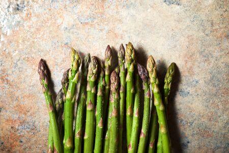 Wild asparagus on a ochre table.