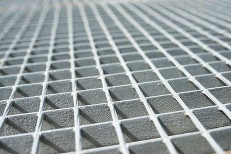 Close-up of a gray metal grating.