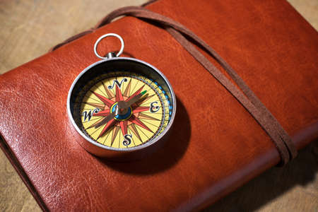 Vintage compass on a leather notebook. 免版税图像