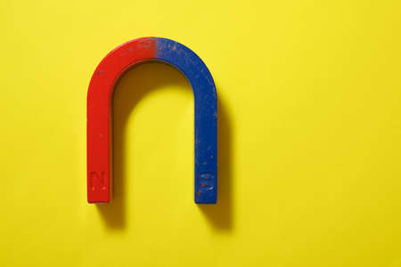 Horseshoe magnet on a yellow table.