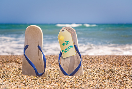Flip flops on the beach with small stones with a tag Hello Summer
