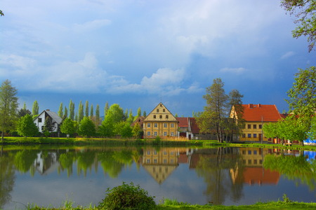 Reflection of houses on the water surface in the town of Ustek. Blue sky with clouds. Czech landscape.