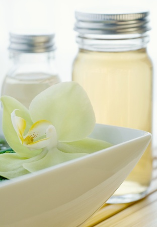 Beautyfull decorative flower with massage oils and lotions in small bottles Stock Photo