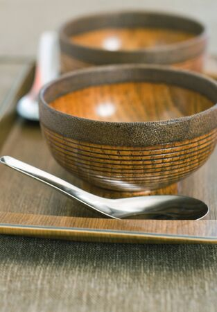 Wooden plates for soup and metalic spoon on wooden board