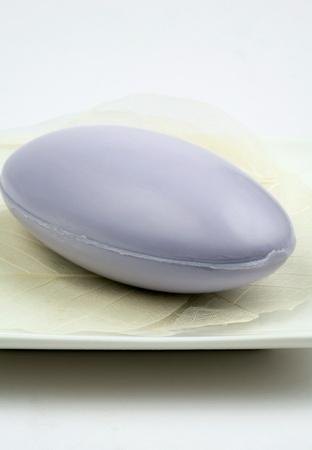 Purple eg shaped soap on square white plate, extreme clouse-up