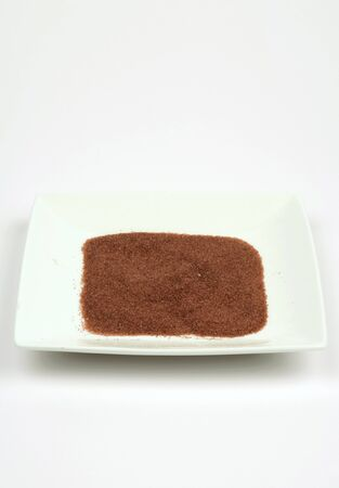 Special bath salt on square white plate, extreme clouse-up Stock Photo
