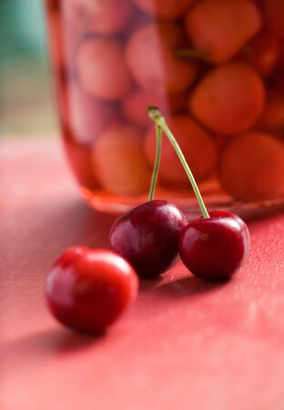 Two juicy red cherries on a red table, with abstract background