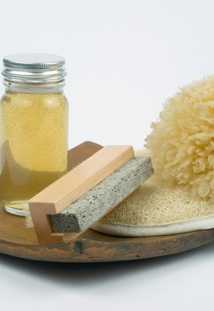 Massage oil sponge and other tools for spa use on wooden board photo