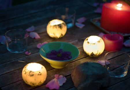 Candles glowing on table decorated with rose petals, and bowl holding floating flower, extreme close-up photo