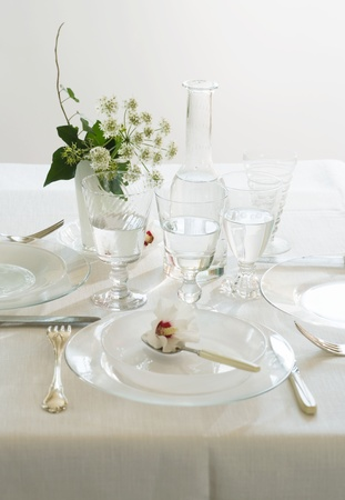 Dinner set on white table, with crystal glasses and fresh flower