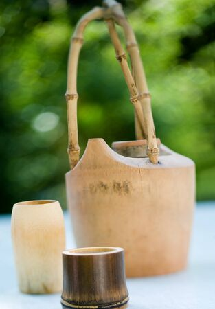 Wooden tea pot with bamboo cups on table outside