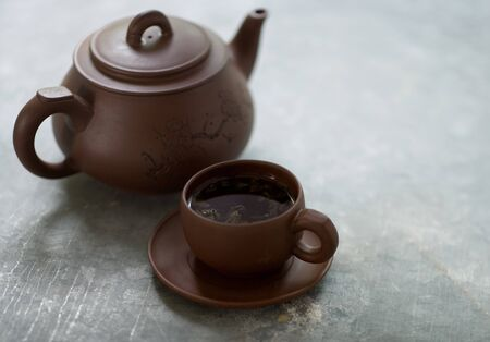 Wooden teapot with wooden cup full of aromatic tea