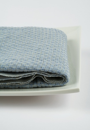 Baby blue square shaped towel on square white dish, extreme close-up