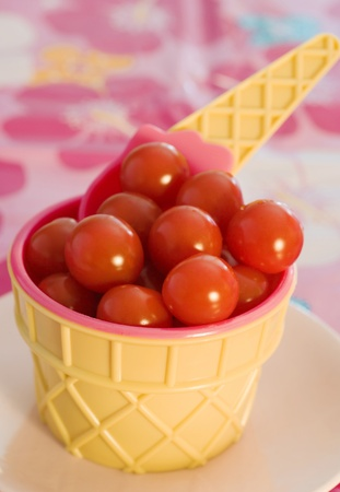 Ice cream cone bowl containing cherry tomatoes with wafle spoon