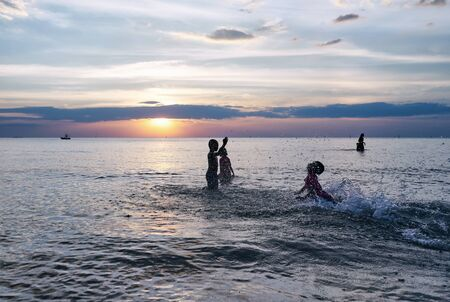 Silhouette of children playing on the beach at sunset                      Stock Photo