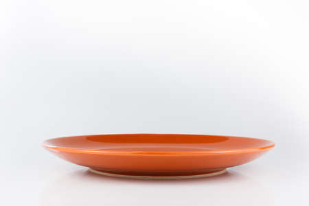 front desk: Orange empty plate. Isolated on white background