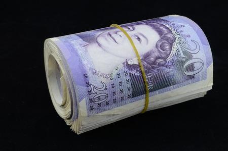 Roll of British twenty pound notes on black background photo