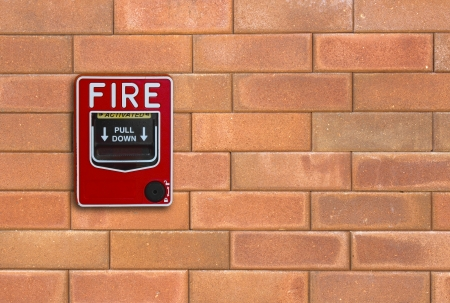 sprinkler alarm: fire break glass on the brick wall background