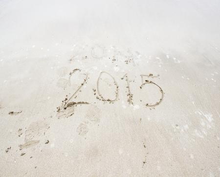 Year 2015 number written on sandy beach photo