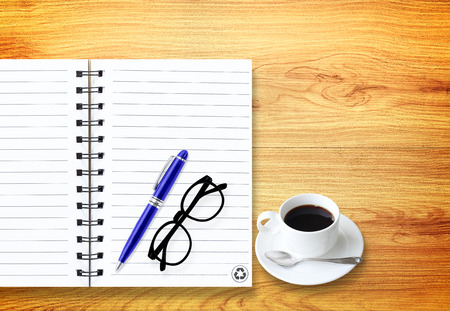 Notebook with office supplies with pen with glasses and cup of coffee on wooden table. photo