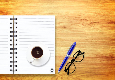notebook with pen and glasses isolated on wood photo
