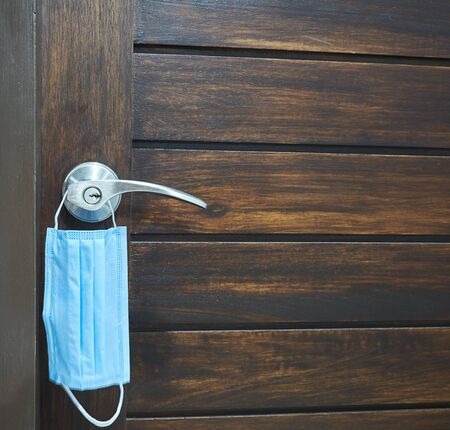 Mask hanging at the door handle for prevention of coronavirus infection