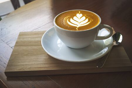 Cup of coffee latte art on wooden background. Beautiful foam, place for text.