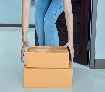 Woman pick up the parcel box to door contactless delivery during a pandemic covid. Online shopping, Quarantine .