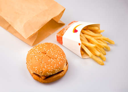 Fast food packaging with hamburger, french fries with brown paper bag on the table isolated on white background