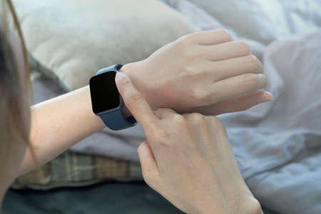 Closeup image of a woman wearing wireless Smart Watch and using smart phone on sofa Stok Fotoğraf