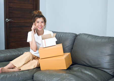 Asian young woman sitting on couch shopping online at home with laptop computer and working from home, Social Distancing Concept.