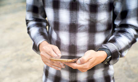 Young man stand and using mobile smart phone.