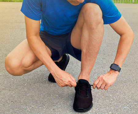 A young Asian man is lacing a shoe at the park to jog in the evening. Stok Fotoğraf
