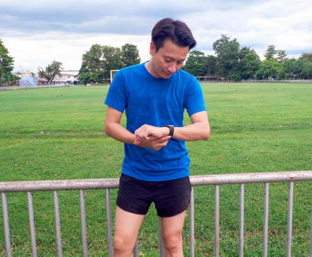 Portrait of a young man in sportswear using his smart watch after training.