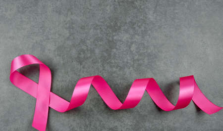 Breast cancer awareness pink sign symbol with face mask on isolated grey background. healthcare and medicine concept.