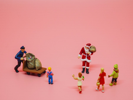 Miniature santa claus, a man with trolly and children on pink background. Christmas and Happy New Year concept
