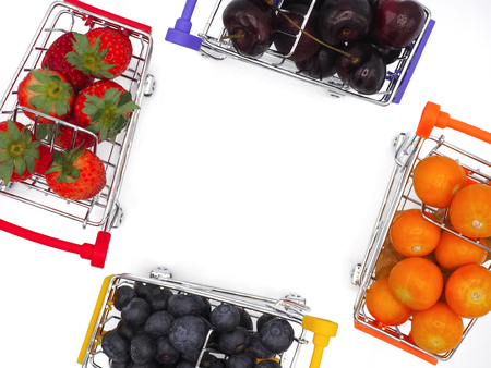 Fresh summer fruits, Cherry, strawberry, cape gooseberry and blueberry in shopping cart or trolly isolated on white background.