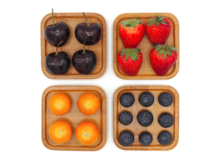 Fresh summer fruits, Cherry, strawberry, cape gooseberry and blueberry in wooden plate isolated on white background.