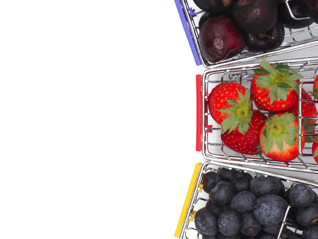 Fresh summer fruits, Cherry, strawberry, and blueberry in shopping cart or trolly isolated on white background.