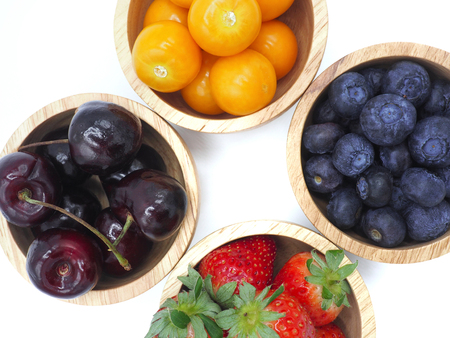 Fresh summer fruits, Cherry, strawberry, cape gooseberry and blueberry in wooden bowl isolated on white background. Archivio Fotografico