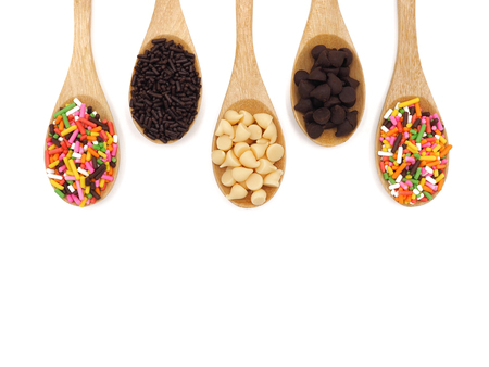 Wooden spoon with chocolate chips and sprinkles on white background. top view