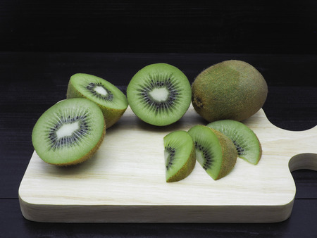 Slice of fresh juicy delicious and healthy kiwi fruits on wooden chopping board, on black wood background.