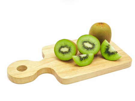 Slice of fresh juicy delicious and healthy kiwi fruit on wooden chopping board, isolated on white background.