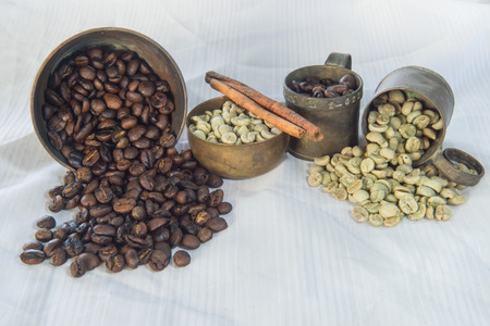 table linen: raw and roasted coffee beans on white table linen Stock Photo