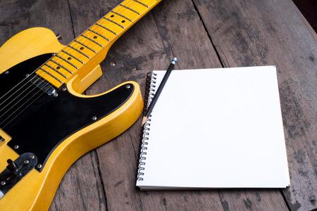 lapiz y papel: telecaster guitarra eléctrica con el bloc de notas en el escritorio de madera